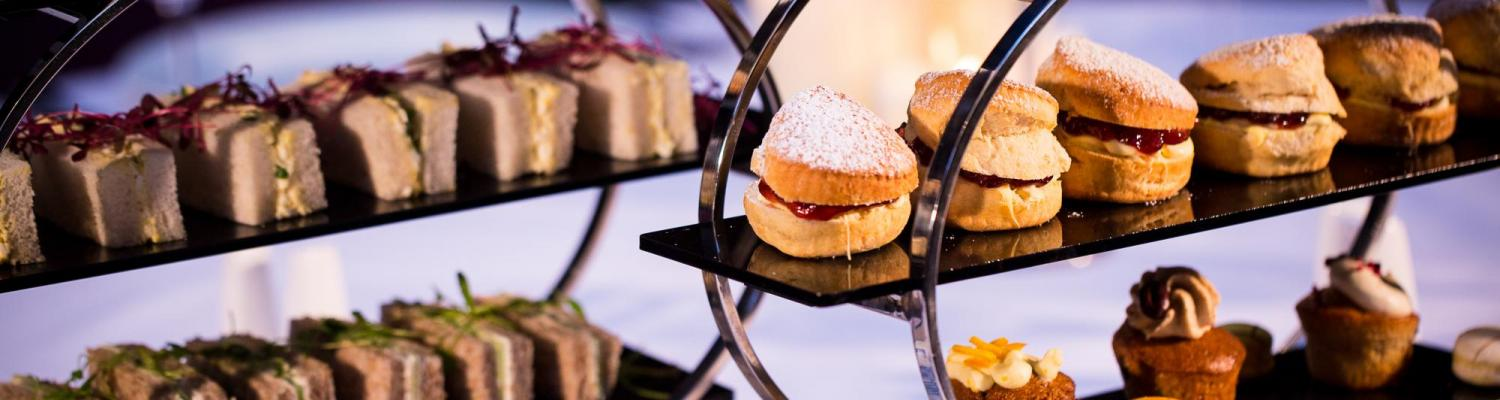 finger sandwiches, homemade cakes and scones with clotted cream and jam